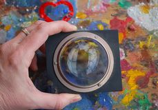 Magnifying glass on the old painting palette with red heart shaped stock images