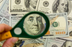 Magnifying Glass on one hundred dollars Stock Photo