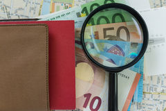 Magnifying glass on one pile of Euro banknotes with document on Stock Photos