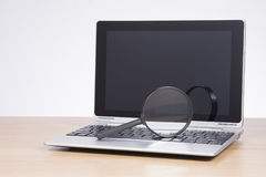 Magnifying glass on open laptop stock image