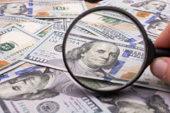 Magnifying glass over the banknote bundle of US dollar Royalty Free Stock Photos