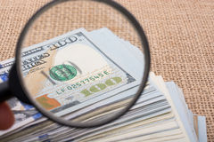 Magnifying glass over the banknote bundle of US dollar Stock Images