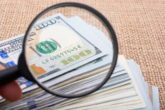 Magnifying glass over the banknote bundle of US dollar Royalty Free Stock Image