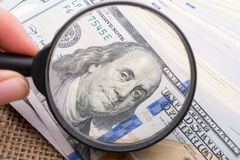 Magnifying glass over the banknote bundle of US dollar Stock Image