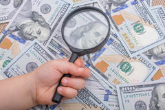 Magnifying glass over the banknote bundle of US dollar Stock Photography