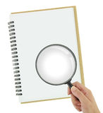 Magnifying glass over blank notebook Stock Image