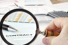 Magnifying Glass Over Contract Papers Royalty Free Stock Images