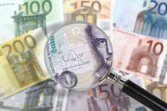 Magnifying glass over euro notes. German mark in the foreground. EU economy under German custody. Financial crisis concept Stock Image