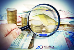 Magnifying glass over euro notes. Man holding a mafnifying glass over euro notes Royalty Free Stock Photo