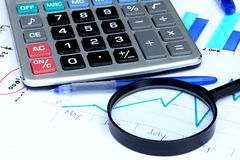 Magnifying glass over financial chart. Magnifying glass placed over financial statistics and charts Stock Photography
