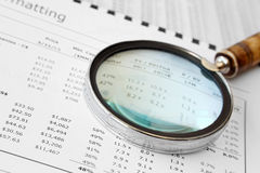 Magnifying Glass Over Financial Document Stock Photos