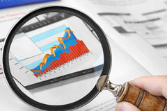 Magnifying Glass Over Financial Graph Stock Images