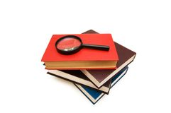Magnifying glass over the stack of books Royalty Free Stock Images