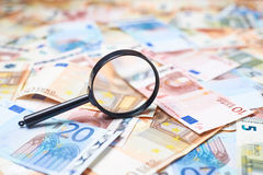 Magnifying Glass Over The Pile Of Money Royalty Free Stock Photo