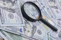 Magnifying glass over   of US dollar the banknotes stock image