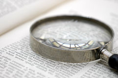 Magnifying glass on page. An older magnifying glass rests on the page of a large book stock photo