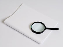 Magnifying glass & paper. Magnifying glass & white paper on plane background Royalty Free Stock Images