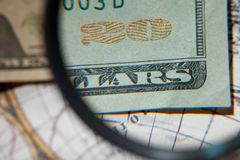 Magnifying glass and paper currency Stock Photo
