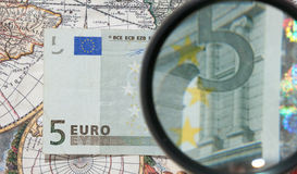 Magnifying glass and paper currency Stock Photography