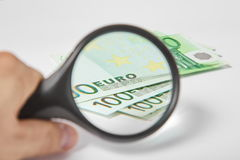 Magnifying Glass on the paper Euros. Magnifying Glass on the one hundred Euros Stock Photos
