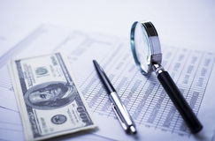 Magnifying glass, pen and analytical financial report lying on a table Royalty Free Stock Photography