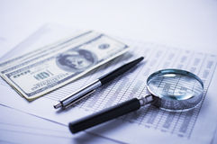 Magnifying glass, pen and analytical financial report lying on a table Royalty Free Stock Photo