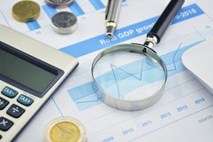 Magnifying glass, pen and calculator on financial chart and grap Royalty Free Stock Images