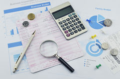 Magnifying glass, pen and coin on graph paper, saving concept Royalty Free Stock Images