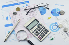 Magnifying glass, pen and coin on graph paper, saving concept Royalty Free Stock Photography