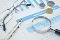 Magnifying glass, pen and glasses on financial chart and graph Royalty Free Stock Images