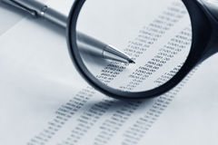 Magnifying glass  and pen over financial report. Magnifying glass over financial report Stock Image