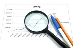 Magnifying glass, pen, pencil and graph. A magnifying glass, pen, pencil and graph. The image idea for business concept Stock Photography