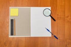 Magnifying glass, pen, pencil lie on notebook. School. Stock Photos