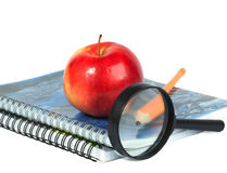 Magnifying glass, pencil and red apple. On spiral notebooks. Shallow depth of field Royalty Free Stock Photos