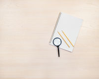 Magnifying glass, pencils and notepad on wooden background. Royalty Free Stock Images