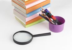 Magnifying glass, pencils and stack of books on white background royalty free stock photography
