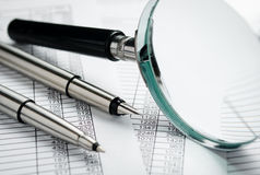 Magnifying Glass and Pens on Top of Reports Stock Photos