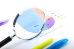 MAGNIFYING GLASS ON A PIE CHART WITH PENS Stock Images
