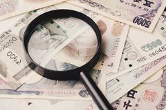 Magnifying glass on pile of asian leading countries new emerging. Market money banknotes, Indian rupee, Chinese yuan and Japanese yen, analyze, invest or royalty free stock photo