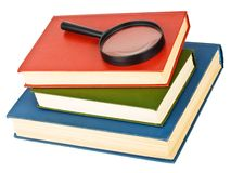 Magnifying glass on a pile of books Stock Photos