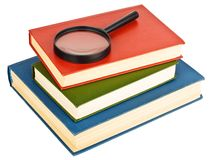 Magnifying glass on a pile of books Royalty Free Stock Photography