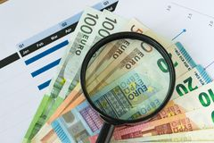 Magnifying glass on pile of Euro banknotes with printed quarter Stock Photo