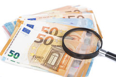 Magnifying glass and pile of euro notes. On white background Stock Photography