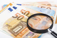 Magnifying glass and pile of euro notes. On white background Royalty Free Stock Photography