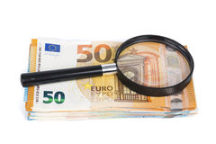 Magnifying glass and pile of euro notes. On white background. Top view Stock Photography