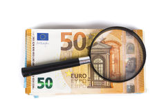 Magnifying glass and pile of euro notes. On white background. Top view Royalty Free Stock Image