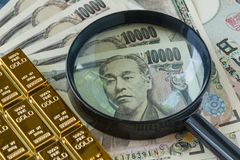 Magnifying glass on pile of japan yen banknotes and gold ingot a Royalty Free Stock Photography