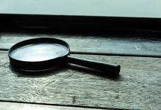 Magnifying glass is placed on a wooden table. royalty free stock images