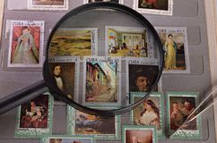 Magnifying glass on a postage stamp. In the album philatelist Royalty Free Stock Photos