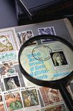 Magnifying glass on a postage stamp. In the album philatelist Royalty Free Stock Images